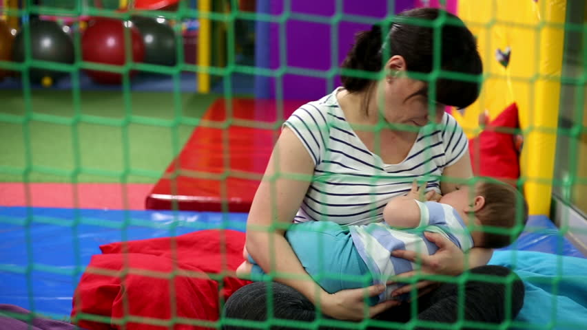 Mother is breastfeeding a baby in playground