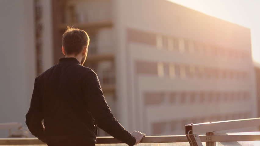 The man standson in the balcony of his luxury apartment. by sunset background.   | Shutterstock HD Video #15662293