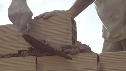 Building brick block wall on construction plant - Mason brick walls were formed by mixing cement trowel to scoop sand and water until a homogeneous poured onto bricks to help the adhesion and strength