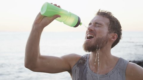 Athlete drinking water from bottle splashing water in face cooling down after fitness running workout on beach. Thirsty man having cold refreshment drink sweating after intense exercise. SLOW MOTION.
