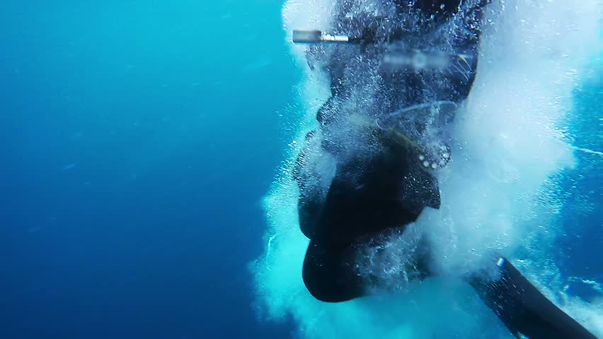 Scuba Diver Jumps From a Dive Boat. High speed camera shot.  In slow motion a scuba diver jumps into water. Scuba Diver Jumping into the Blue Ocean.