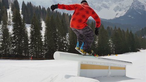 snowboard slow motion,snowboarder riding jumping on kink rail