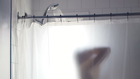 Showering Woman Silhouette Blurred by the Transparent Curtain