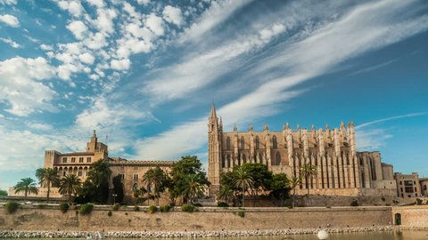 Timelapse with flying clouds over Cathedral of Palma de Mallorca and Almudaina Castle. Beautiful gothic architecture overlooking the sea shore, Mallorca island, Spain.