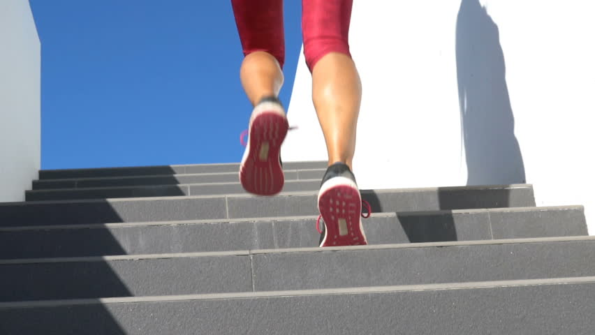 Running on stairs woman doing run up on staircase. Female runner athlete climbing stairs in sport workout run outside. Running shoes and legs close up and zoom out.