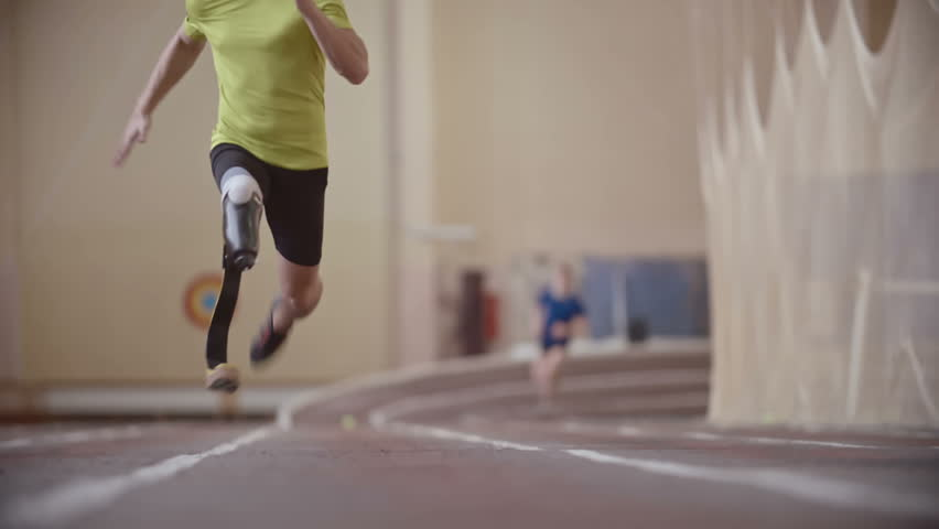 Determined Paralympic athlete with prosthetic leg running a race towards the camera in slow motion