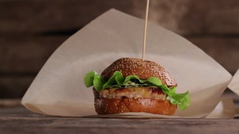 Burgers with sticks on table. Different burgers on wooden background. Food that tastes good. Daily calorie norm.