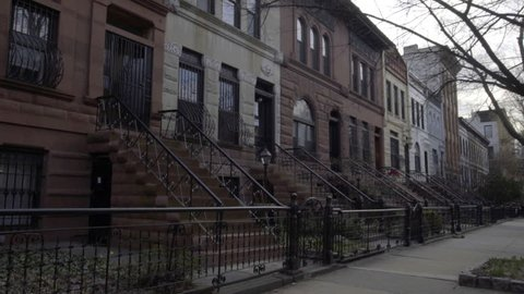 An establishing shot of a row of Brownstone homes in Brooklyn, NYC. New York, NY - March, 2016