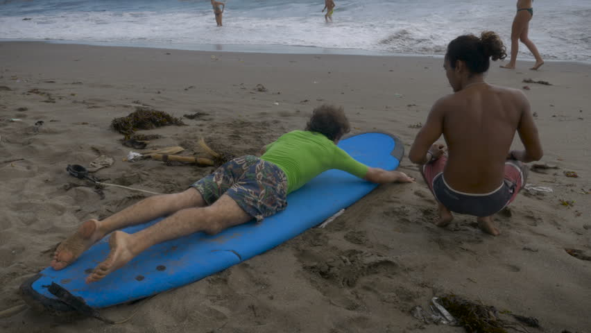 Learning how to get up on a surf board during a beginning surf lesson in Bali