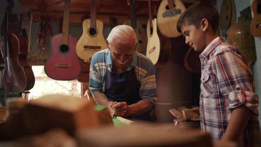 Old and young people showing love for music. Boy and senior man, happy kid and elderly person, grandpa teaching grandchild how to chisel wood for guitars and instruments. Traditional profession