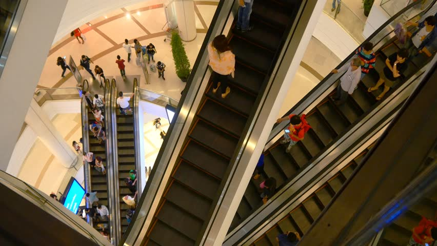 Escalator 4k shopping mall crowd of people buy shop center centre last minute sales christmas shopping frenzy big indoors complex