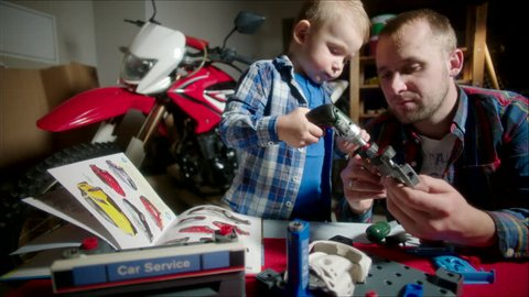 Father and Son Screwing Wheels to the Toy Car