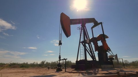 CLOSE UP: Industrial oil pump jack working and pumping crude oil for fossil fuel energy with drilling rig in oil field. Nodding donkey pump against the blue sky pumping over the sun in sunny summer