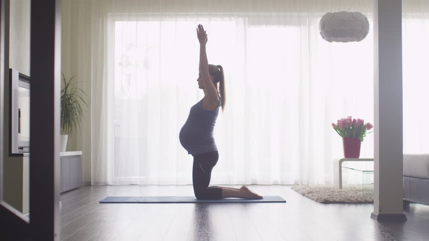 Young Pregnant Woman Doing Stretching and Fitness in Living Room at Home. Shot on RED Cinema Camera. | Shutterstock HD Video #15905305