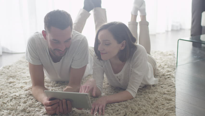 Man and Woman laying on Floor and using Tablet for Entertainment. Shot on RED Cinema Camera. | Shutterstock HD Video #15905668