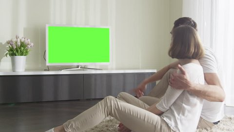 Couple Watching TV with Green Screen. Great for mockup usage. Shot on RED Cinema Camera.
