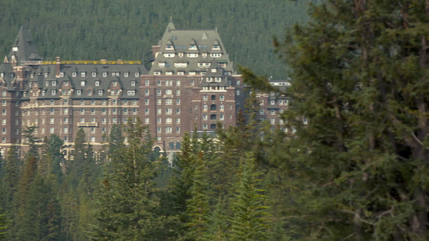 Long shot of the Banff Springs Hotel with Evergreen trees in the foreground framing the hotel.  Banff Alberta