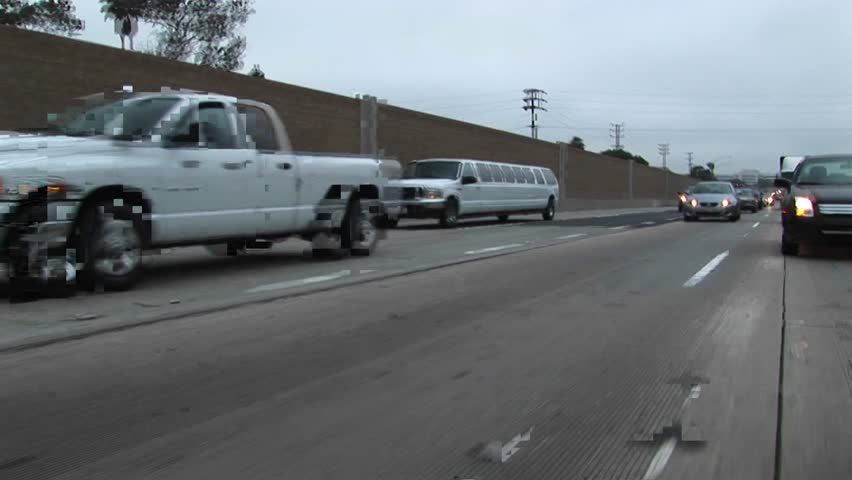 A stretch limo drives down a freeway