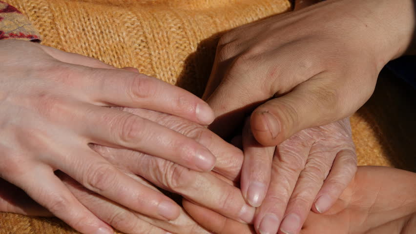 Many hands comforting a old pair of hands outdoor. | Shutterstock HD Video #15949261
