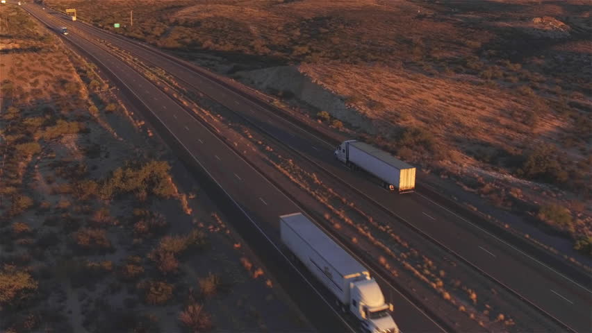 4K AERIAL: Flying high above container semi truck transporting goods on busy highway across the country in beautiful summer evening. Traffic driving and speeding on busy freeway at golden sunset #15953452