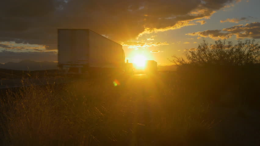 4K CLOSE UP: Personal cars and big freight transporting semi trucks driving on busy highway at beautiful golden sunset in summer. Traffic on busy freeway speeding over the setting sun.