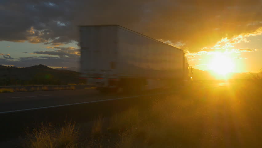 4K CLOSE UP: Freight semi truck speeding on empty highway over golden sun at summer sunset. Transporting truck driving on freeway in sunny morning. #15953584