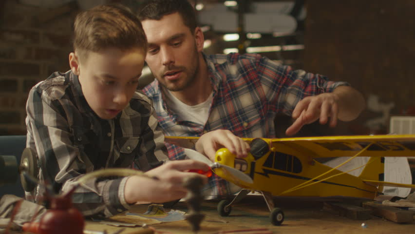 Father and son are modeling a toy airplane in a garage at home. Shot on RED Cinema Camera in 4K (UHD). | Shutterstock HD Video #15989338
