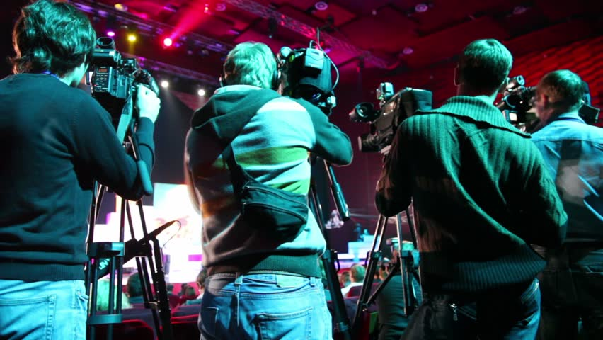Operators on workplace in row of few cameras, view from behind on event