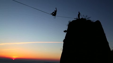 Aerialist Balances on Tightrope at Sunset
