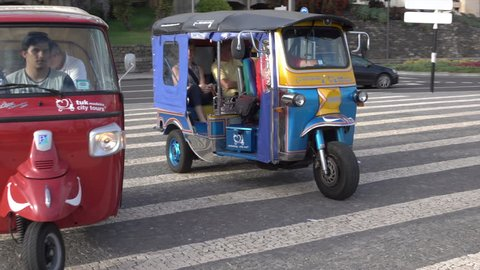 FUNCHAL, MADEIRA/PORTUGAL - JANUARY 23, 2016: Unidentified people take tuk tuk tour of the city. The island is popular with tourists who come here for the mild climate and fresh flowers.