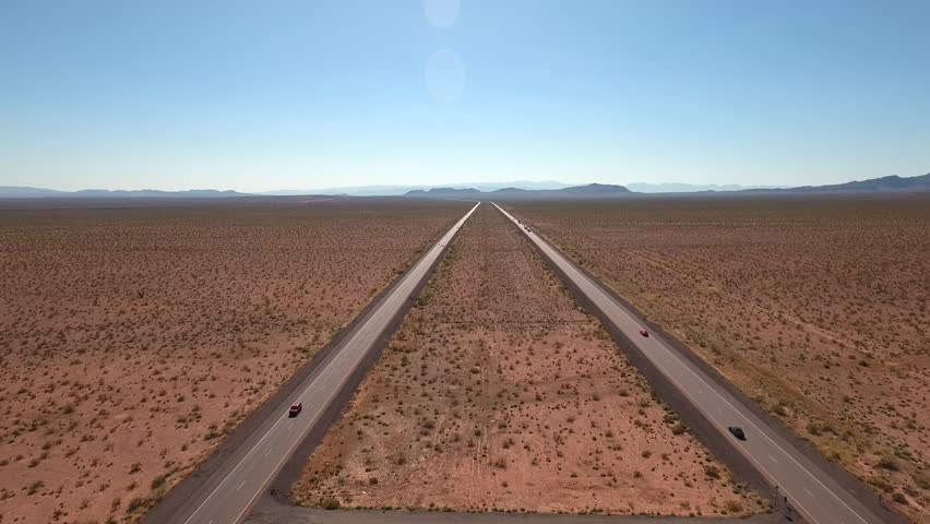 An aerial shot of cars and trucks traveling through the desert of Nevada near Las Vegas on Interstate 15 | Shutterstock HD Video #16022098