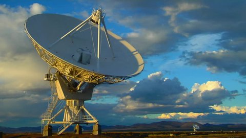 A satellite dish moves in time-lapse against a beautiful sky