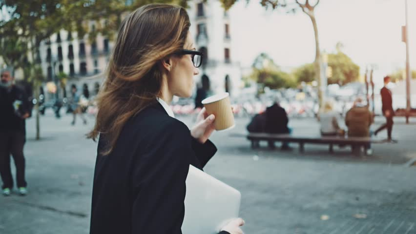Close-up of young professional businesswoman walking outdoors, drinking coffee to go and holding modern portable computer or laptop, slow motion | Shutterstock HD Video #16045819