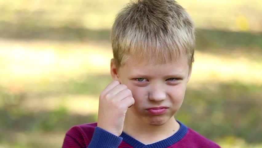 Close up portrait of funny 8 years old boy over green trees background. Boy making angry face and trying not to laugh.  Portrait of cute kid looking at camera. Real time video footage
