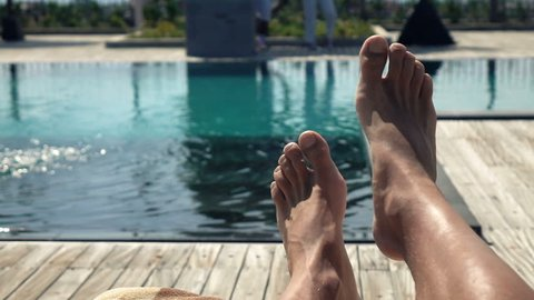 Male feet on daybed by swimming pool, super slow motion 240fps