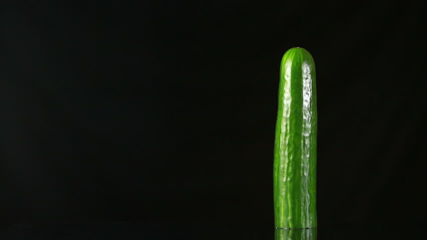 Woman's hand dress the condom on cucumber