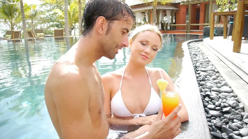 Married couple drinking cocktail in resort pool