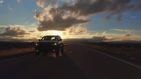 AERIAL: Black SUV car driving along the picturesque empty road through the vast desert at beautiful golden sunset. People traveling, road trip through beautiful countryside scenery in sunny summer