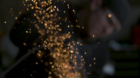 A shower of sparks is thrown from an angle grinder in an industrial workshop in extreme SLOW MOTION, mechanic or engineer out of focus in background