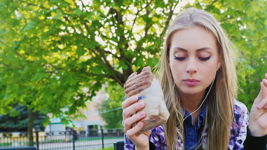 Attractive woman eating a sandwich in the park, listening to music
