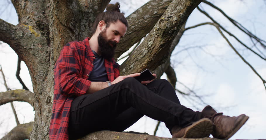 4k young carefree man sitting on a tree trunk away from hustle and bustle of a city and browsing the internet on a touchscreen tablet. | Shutterstock HD Video #16143202