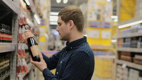 Young man chooses beer in the supermarket