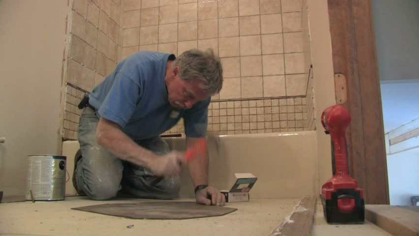 Man fixes bathroom floor.