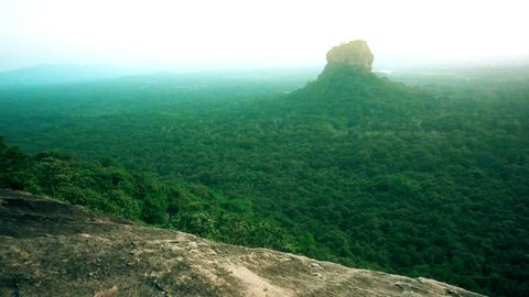 Lion Rock in Sigiriya, Sri Lanka. Aerial view of the tropical forest with mountains. Tilting shot, slow motion.