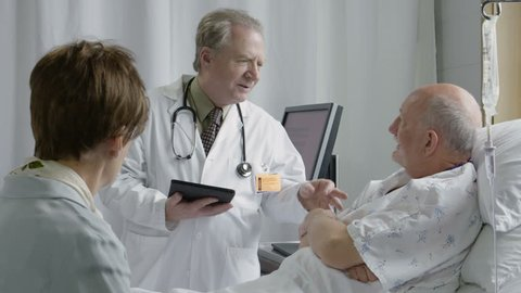 Medical doctor giving good news to couple in the hospital