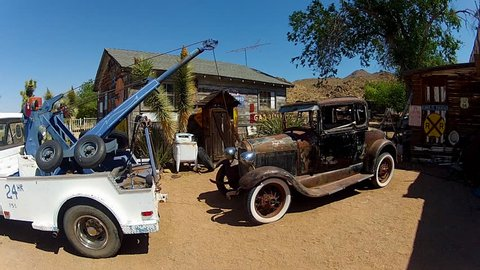 HACKBERRY, ARIZONA/USA- June 14, 2015- A tow truck and an old Model T car attract attention to a roadside mechanic / car repair garage / salvage yard / junkyard in the Arizona desert.