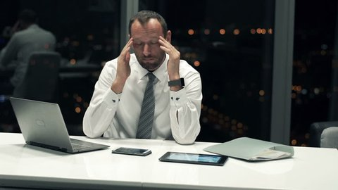 Young businessman having head pain during work in office, by night,