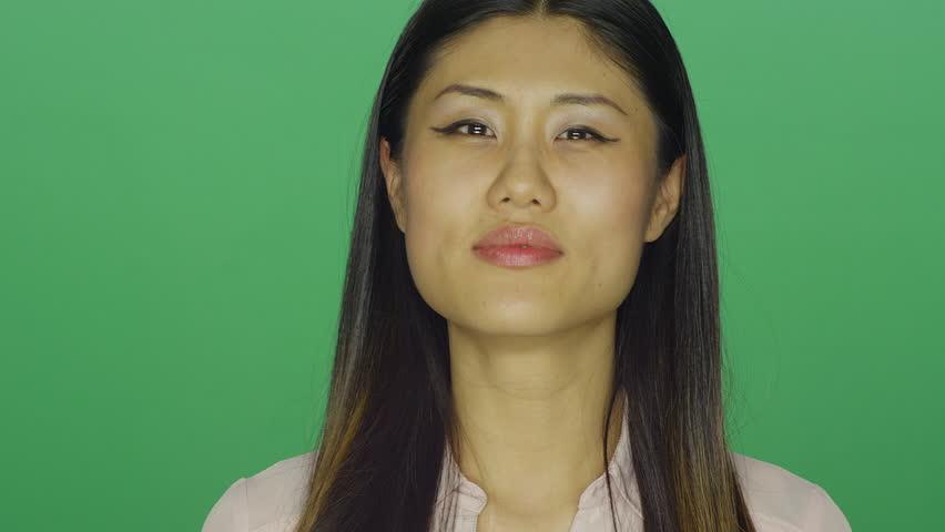 Beautiful Asian woman smiling, on a green screen studio background | Shutterstock HD Video #16253608