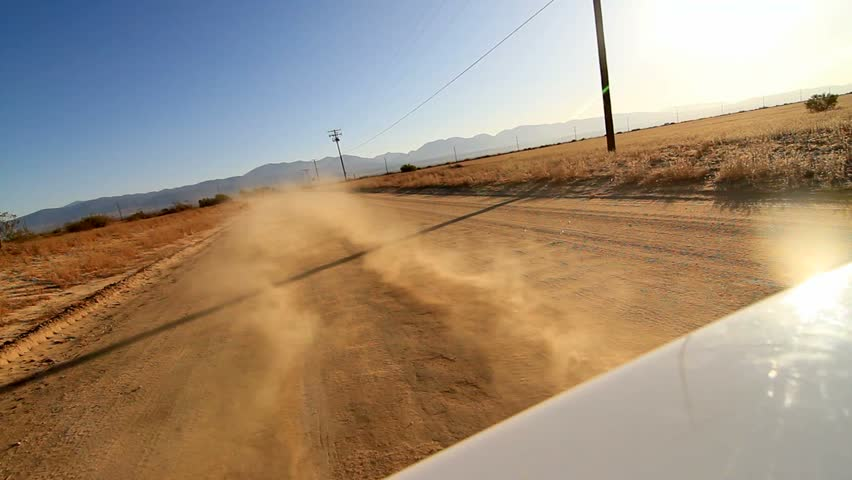 Camera attached on the back of a car while driving on desert dirt road