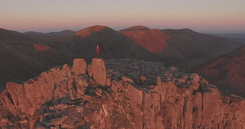 AERIAL: Climber on summit of a mountain at dawn in Snowdonia, UK